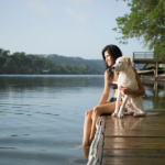 a woman with a dog near the lake