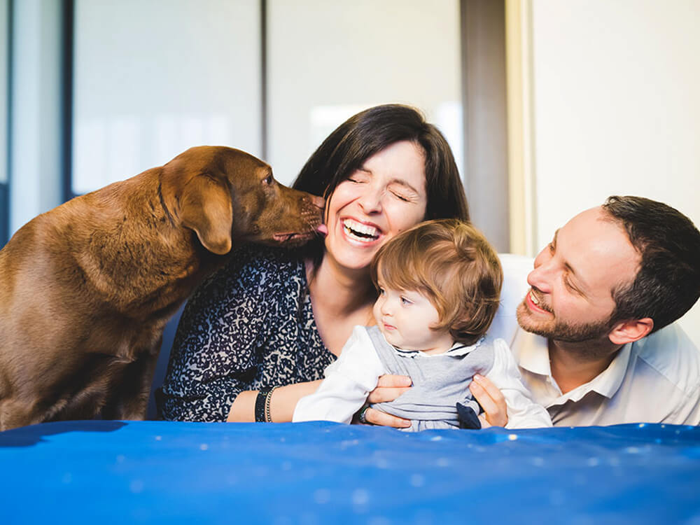 family and a dog licking woman's face