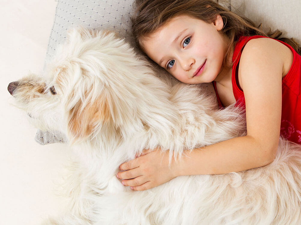 girl cuddling dog in bed