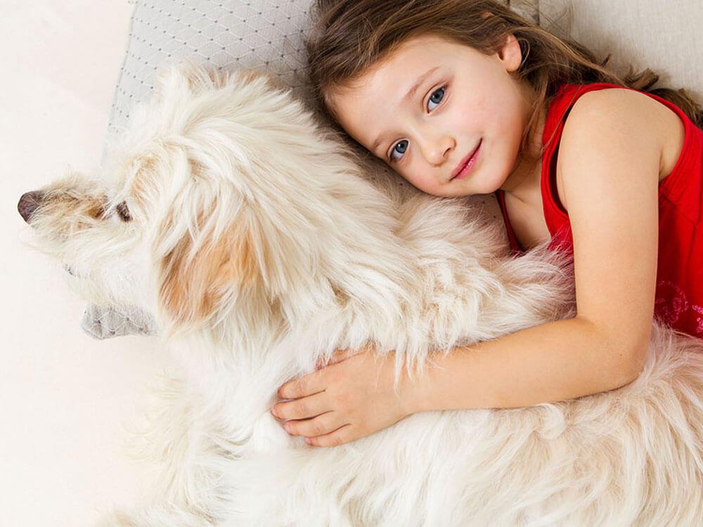 girl cuddling dog in bed