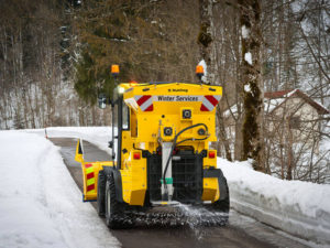 Winter service vehicle removing snow from the road