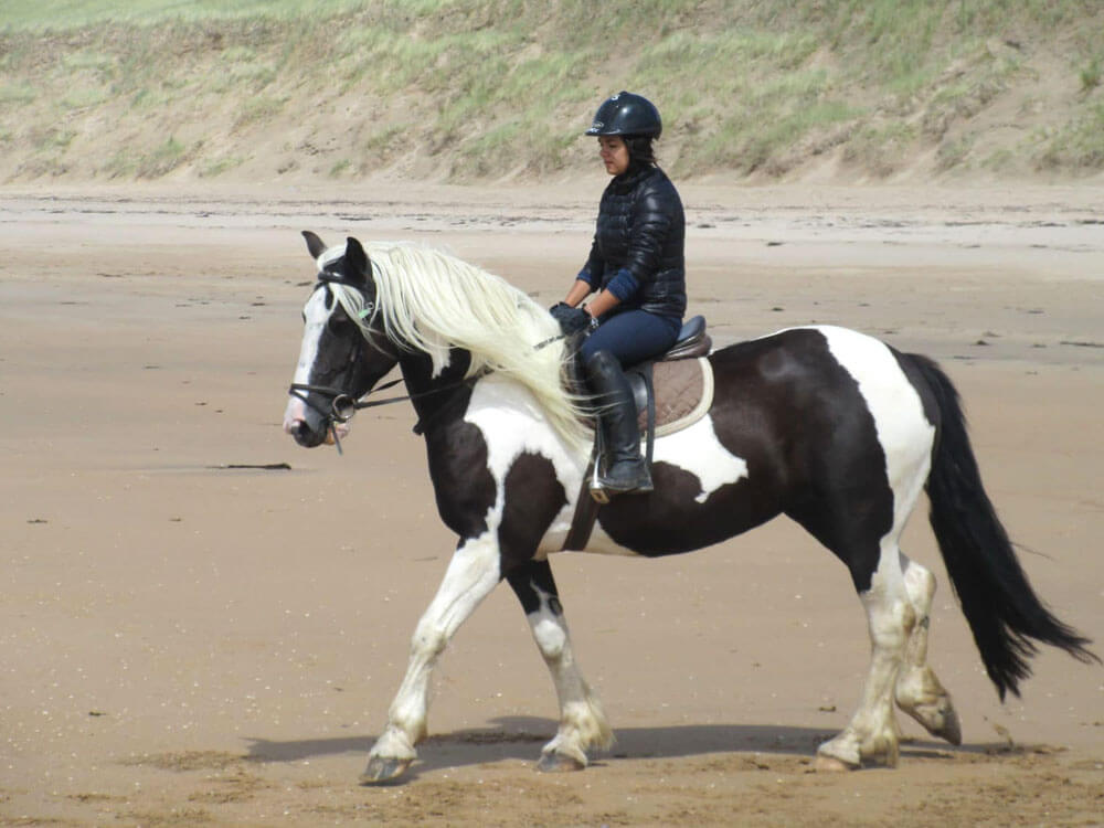 a woman wearing the right clothing when horseback riding