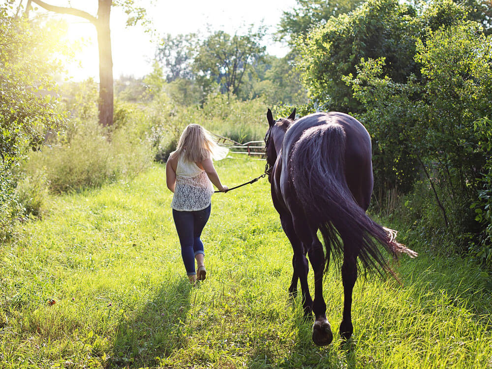 A woman together with her horse going for a walk side-by-side