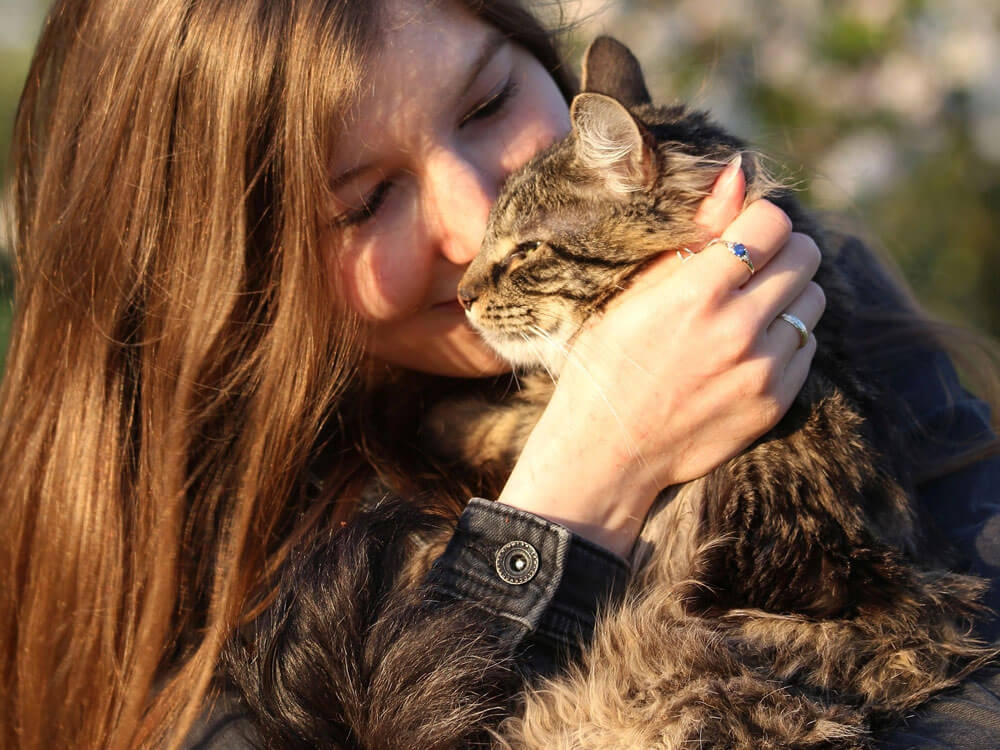 a woman with her cat post for a photo