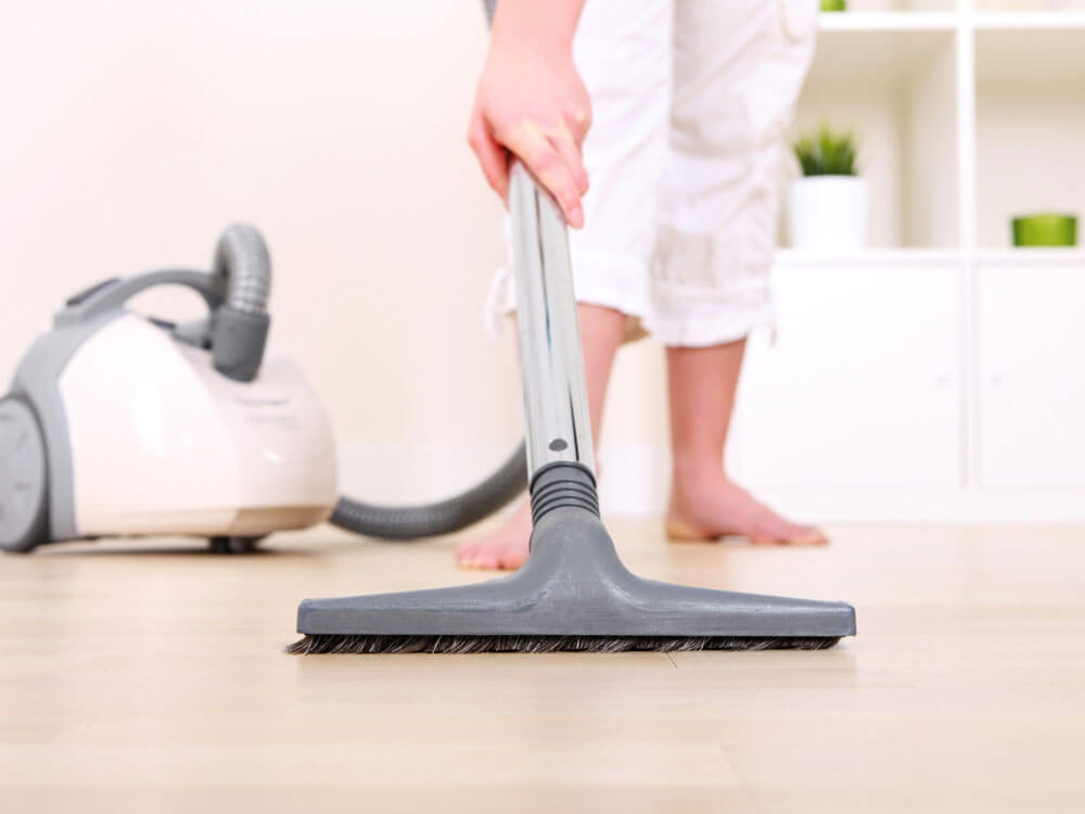 a woman vacuuming her home