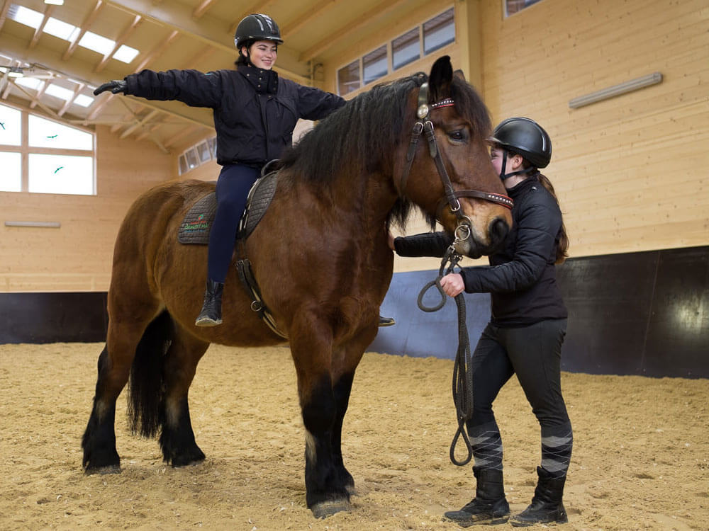 horse riding practice with the help of a woman