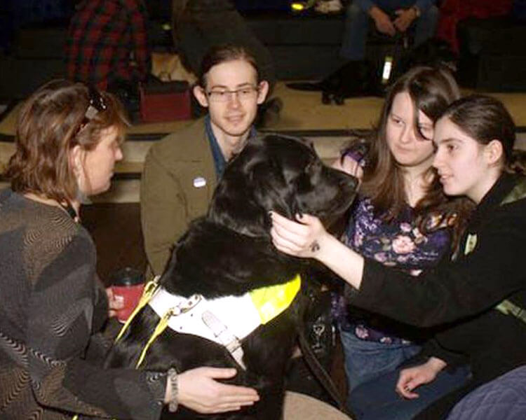 bangor university students cuddling a hound dog