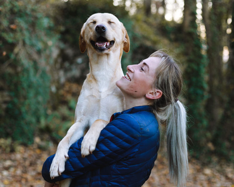 a happy dog carried by a woman
