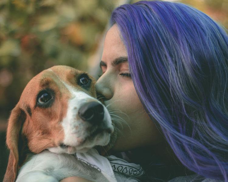 a girl kissing her dog's cheek