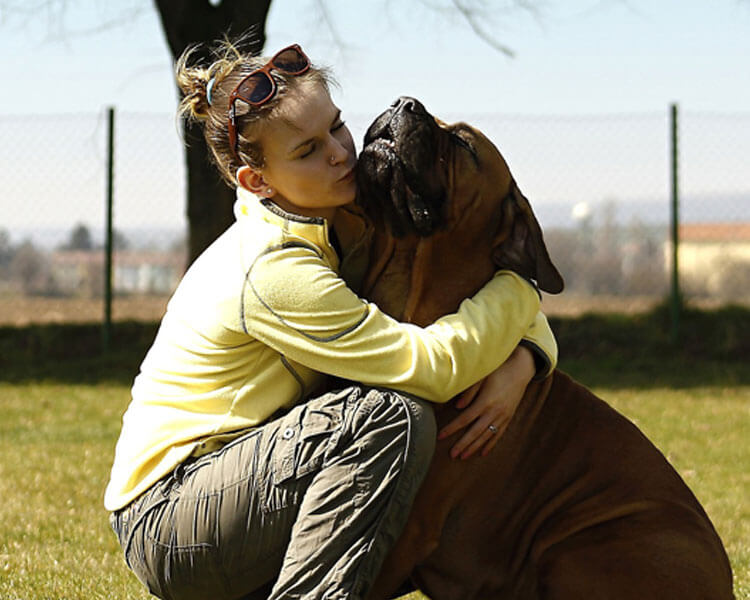 a woman hugging her dog at the park