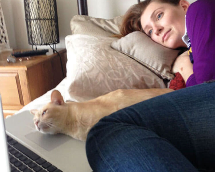 a woman and her cat lying in bed while watching on the laptop