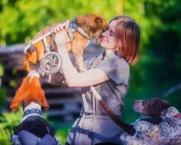 Daria Pushkareva with two dogs and one disabled dog she carried
