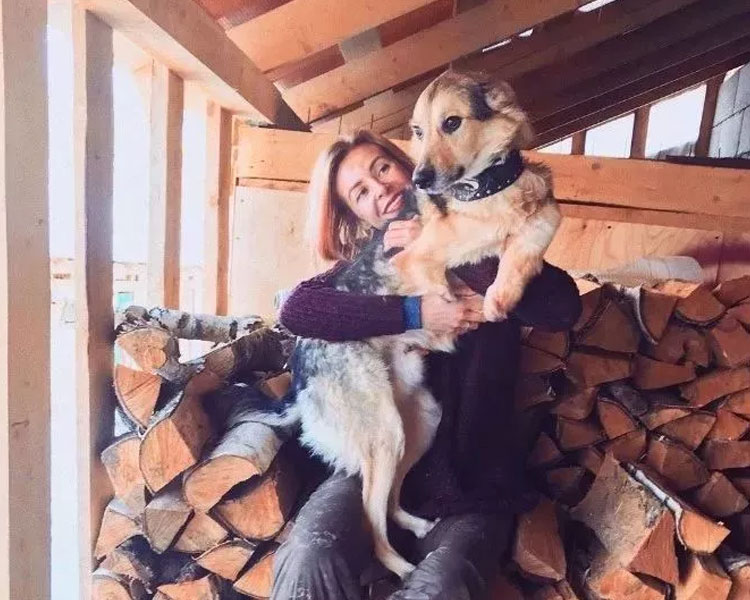 Daria carries one of her dogs in front of a stock of woods