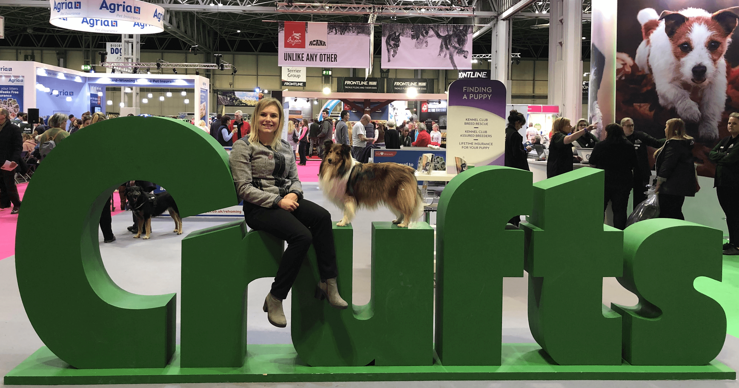 a woman with her dog sitting in a crufts standee